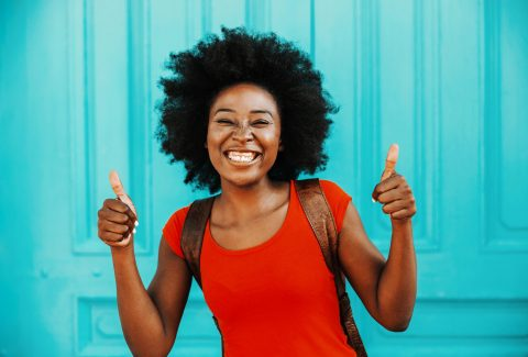 Young smiling gorgeous african woman with short curly hair standing outdoors and showing thumbs up. Diversity concept.