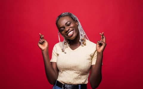 Beautiful young Afro American woman is holding fingers crossed and smiling, isolated on red background